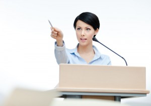 woman speaking at conference podium